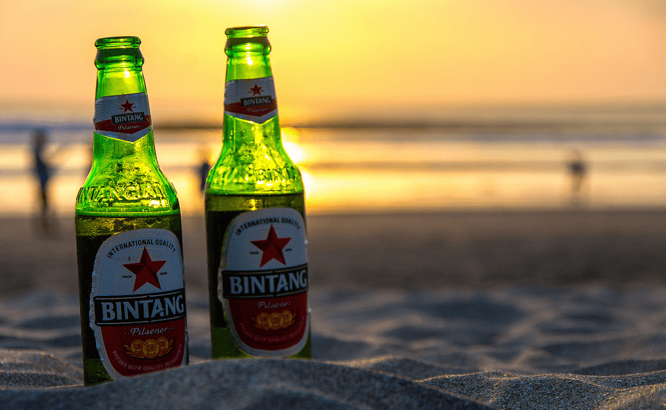 Two Bintang beers on resting on the sand at sunset.